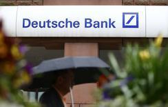 Un hombre camina junto a una oficina de Deutsche Bank, en Hanau, Alemania. 27 de abril de 2015. Deutsche Bank podría necesitar más capital para fortalecer su posición financiera, después de informar que prevé una pérdida neta récord de unos 6.700 millones de euros (7.300 millones de dólares) para el 2015 debido a amortizaciones, gastos por litigios y costos de reestructuración. REUTERS/Kai Pfaffenbach/Files