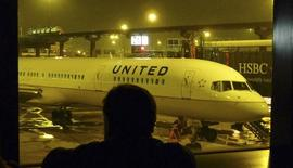 A passenger looks at a United Airlines airplane, painted with its new corporate logo, at a gate at Liberty International Airport in Newark, New Jersey February 7, 2011. .    REUTERS