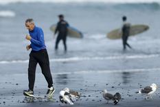 An elderly man exercises with a jog along the beach as surfers head into the ocean in La Jolla, California January 20, 2016.  REUTERS/Mike Blake