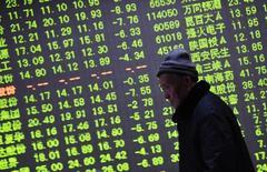 Un inversor camina junto a una pantalla electrónica que muestra información bursátil, en una correduría en Hangzhou, China. 21 de enero de 2015. Las frágiles acciones chinas cerraron con un alza el viernes, en una respuesta relativamente moderada a señales de más políticas de estímulo en Europa y Japón que motivaron un fuerte rebote en los precios del petróleo y las acciones en otras partes.REUTERS/China Daily