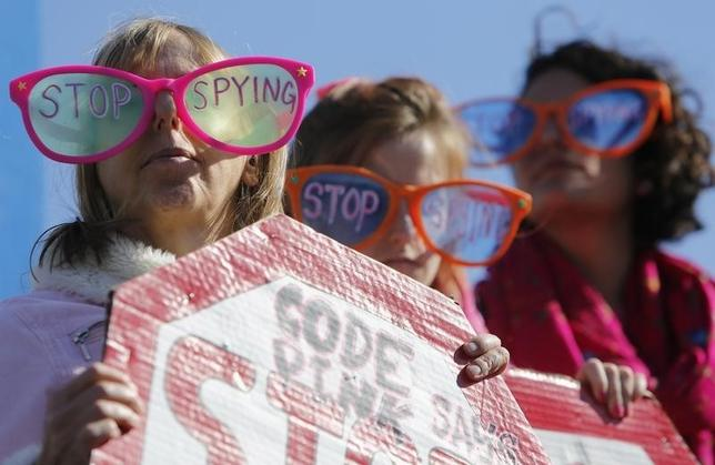 Demonstrators from the organization Code Pink wear toy glasses reading ''Stop Spying'' at the ''Stop Watching Us: A Rally Against Mass Surveillance'' near the U.S. Capitol in Washington, October 26, 2013.   REUTERS/Jonathan Ernst