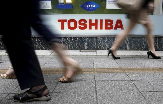 Pedestrians walk past a logo of Toshiba Corp outside an electronics retailer in Tokyo September 14, 2015. REUTERS/Toru Hanai