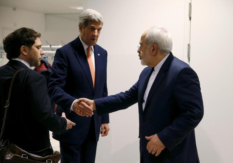 U.S. Secretary of State John Kerry shakes hands with Iranian Foreign Minister Mohammad Javad Zarif after the International Atomic Energy Agency (IAEA) verified that Iran has met all conditions under the nuclear deal, in Vienna January 16, 2016.  REUTERS/Kevin Lamarque