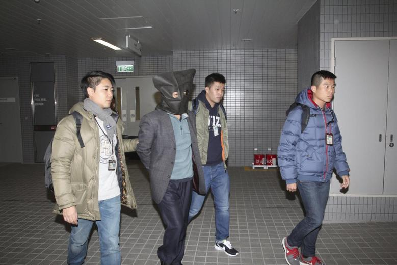 Forty-four-year-old Deyun Shi (2nd L) is escorted by plainclothed police officers in Hong Kong, China January 24, 2016. REUTERS/Apple Daily