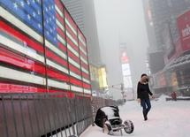 A woman walks during a snowstorm at Times Square in the Manhattan borough of  New York January 23, 2016REUTERS/Shannon Stapleton
