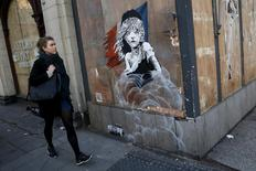 A woman walks past a new graffiti mural attributed to Banksy, opposite the French embassy in London, Britain January 25, 2016.  REUTERS/Stefan Wermuth