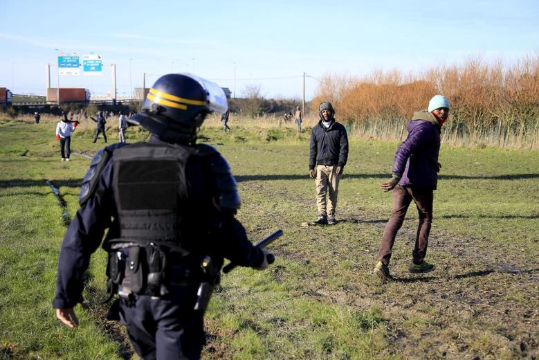 A French riot policeman stops migrants in a field near Calais, France, as migrants gather in the hopes of attempting to board lorries and making their way across the Channel to Britain, January 21, 2016. REUTERS/Pascal Rossignol