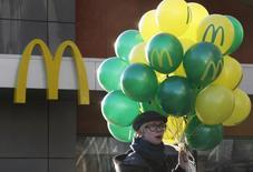 Посетитель у ресторана McDonald's в центре Москвы 19 ноября 2014 года. McDonald's увеличит инвестиции в РФ в 2016 году до примерно 9 миллиардов рублей и откроет не менее 60 ресторанов, наращивая долю в кризис, чему способствует высокая локализация производства, которую компания планирует в будущем довести до 100 процентов. REUTERS/Sergei Karpukhin