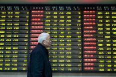 Investidor passa por painel eletrônico com informações de ações em corretora de Nanjing, na China. 26/01/2016 REUTERS/China Daily