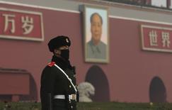 Милицонер у портрета Мао Цзэдуну в Пекине. 9 декабря 2015 года. В отношении главы Национального бюро статистики Китая ведется расследование по подозрению в совершении дисциплинарных нарушений, сообщило антикоррупционное ведомство коммунистической партии Китая. REUTERS/Stringer
