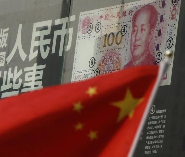 1月26日、中国は人民元の再切り下げを迫られ、人民元の下落率は20─50%になる──。ごく一部の有力ヘッジファンドがこうした大胆な予想に基づいてポジションを構築しつつある。写真は銀行店舗に貼られた100元紙幣のデザインを説明するポスターと中国国旗。北京で21日撮影(2016年 ロイター/Kim Kyung-Hoon)