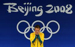 Matthew Mitcham of Australia reacts on the podium before receiving his gold medal for the men's 10m platform diving final at the Beijing 2008 Olympic Games August 23, 2008.     REUTERS/Wolfgang Rattay