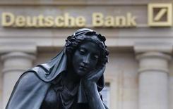 Памятник на фоне логотипа Deutsche Bank во Франкфурте-на-Майне. 26 января 2016 года. Глава Deutsche Bank Джон Крайан призвал инвесторов отнестись с пониманием к изменениям, которые ждут крупнейшего кредитора Германии в 2016 году, после того, как он получил рекордный убыток за прошлый год. REUTERS/Kai Pfaffenbach