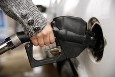 A woman pumps gas at a station in Falls Church, Virginia December 16, 2014.  REUTERS/Kevin Lamarque