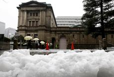 People holding umbrellas walk in front of the Bank of Japan building after snowfall in Tokyo, Japan January 18, 2016. REUTERS/Toru Hanai