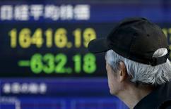 Un hombre camina junto a un tablero electrónico que muestra el índice Nikkei, afuera de una correduría en Japón. 20 de enero de 2016. El índice Nikkei de la bolsa de Tokio saltó el viernes a un máximo en más de dos semanas después de que el Banco de Japón relajó inesperadamente su política monetaria al introducir una política de tasas de interés negativas. REUTERS/Toru Hanai
