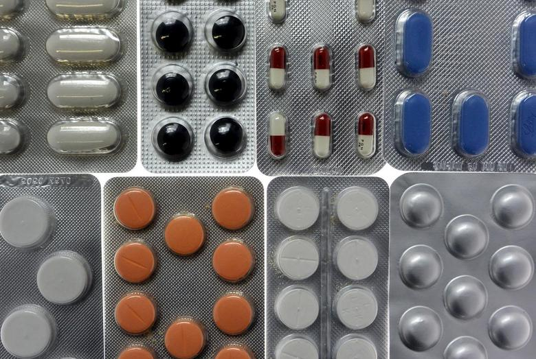 Pharmaceutical tablets and capsules in foil strips are arranged on a table, in this file photo illustration shot in Ljubljana on September 18, 2013. REUTERS/Srdjan Zivulovic/Files