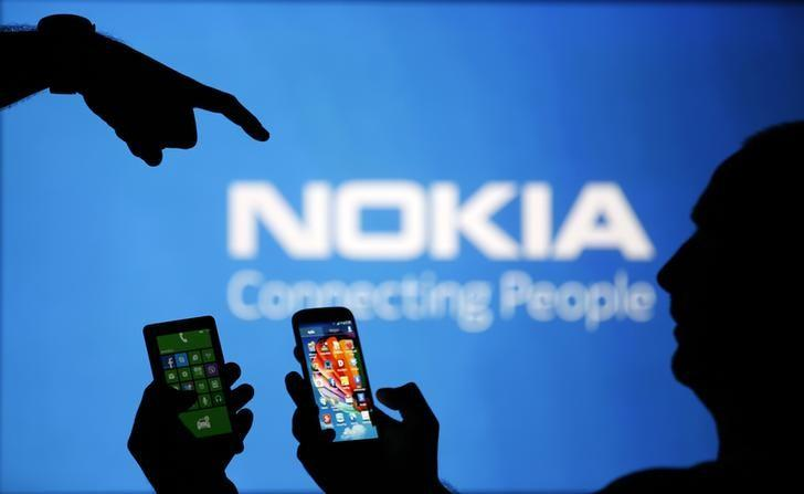 Men are silhouetted against a video screen with an Nokia logo as he poses with an Nokia Lumia 820 and Samsung S4 smartphones in this photo illustration taken in the central Bosnian town of Zenica, August 14, 2013. REUTERS/Dado Ruvic/Files