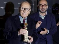"Italian composer Ennio Morricone pose with the Golden Globe trophy he received for his work on the movie ""The Hateful Eight"", as Italian director Giuseppe Tornatore applauds in Rome, Italy January 30, 2016. REUTERS/Tony Gentile"