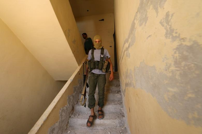 A Nusra Front fighter walks with his weapon inside a building in the Sheikh Maksoud neighbourhood of Aleppo, Syria  August 3, 2015. REUTERS/Abdalrhman Ismail