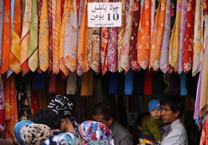Residents select turbans at a shop in downtown Urumqi, Xinjiang Uighur Autonomous Region, May 1, 2014. REUTERS/Petar Kujundzic