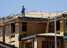 Un trabajador en el techo de una vivienda en construcción en Carlsbad, EEUU, sep 22, 2014. El gasto en construcción en Estados Unidos apenas subió en diciembre debido a que los desembolsos para estructuras no residenciales registraron su mayor caída desde 2013, lo que sugiere una moderada revisión a la baja en la estimación del crecimiento del producto interno bruto del cuarto trimestre.    REUTERS/Mike Blake