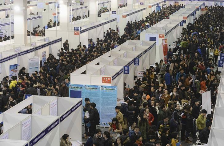 Job seekers visit booths at a job fair in Shanghai January 10, 2015. REUTERS/Stringer