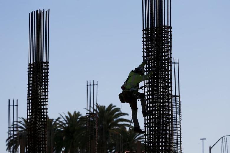 A worker climbs a fixture at a construction site along University Ave in East Palo Alto, California December 16, 2015.  REUTERS/Stephen Lam