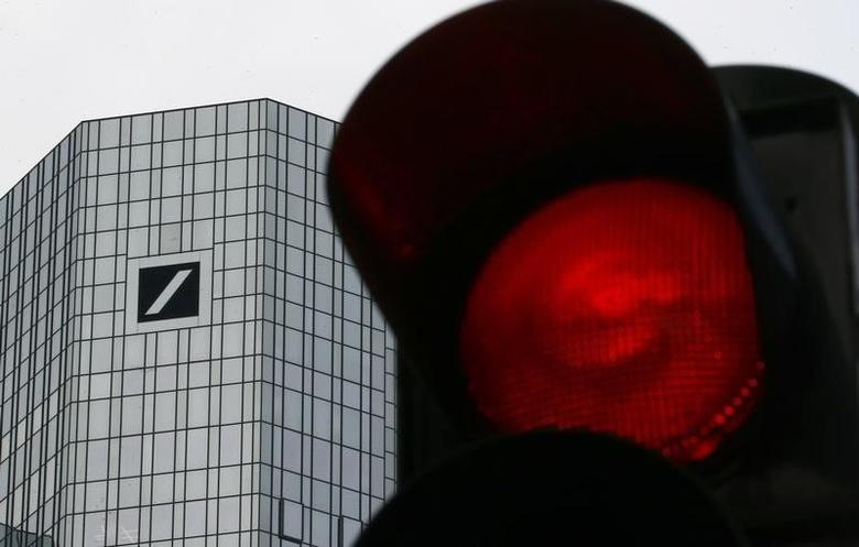 A red traffic light is seen next to the headquarters of Germany's Deutsche Bank in Frankfurt, Germany, January 26, 2016. REUTERS/Kai Pfaffenbach