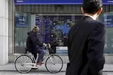 Un hombre en bicicleta mira un tablero electrónico que muestra los índices de mercados de varios países, afuera de una correduría en Tokio, Japón, 4 de febrero de 2016. Las bolsas de Asia subían el jueves en momentos en que la especulación de que la Reserva Federal de Estados Unidos podría optar por no subir las tasas de interés en el resto del año golpeaba al dólar y provocaba un rebote en los precios del petróleo. REUTERS/Yuya Shino