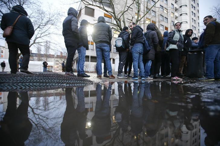 Migrants are reflected in a puddle as they queue in front of the compound of the Berlin Office of Health and Social Affairs (LAGESO) for their registration process, early morning in Berlin, Germany, February 2, 2016     REUTERS/Fabrizio Bensch
