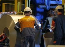 Foto de archivo: Operadores trabajan en una bobina de acero en una fábrica de ArcelorMittal en Florange, Francia, 18 de octubre del 2013. La mayor siderúrgica del mundo anunció planes para recaudar 3.000 millones de dólares en capital nuevo en un intento por reducir su deuda en medio de la debilidad de los sectores siderúrgico y minero. REUTERS/Vincent Kessler