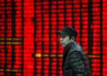 Un inversor camina junto a un tablero electrónico que muestra la información de las acciones, en una correduría en Huaibei, provincia de Anhui, China. 29 de enero de 2016. Las acciones chinas cayeron el viernes por la opinión en el mercado de que las medidas del Gobierno para elevar los límites de inversión a los inversores extranjeros no darán lugar a un aumento inmediato de las compras de valores chinos fuera del país. REUTERS/China Daily