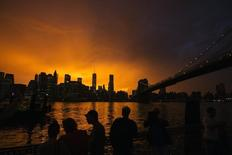 People line a dock in Brooklyn to watch the sun set behind the Manhattan skyline after a summer storm in New York in this July 2, 2014 file photo.  REUTERS/Lucas Jackson