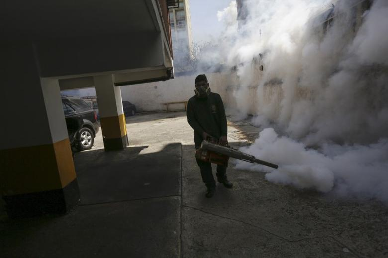A municipal worker fumigates the parking lot of a building to help control the spread of the mosquito-borne Zika virus in Caracas, February 5, 2016. REUTERS/Marco Bello