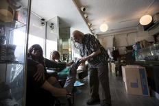 El zapatero Arturo Azinian atendiendo a un cliente en su tienda en Beverly Hills, EEUU, abr 24, 2015. La confianza de las pequeñas empresas de Estados Unidos cayó en enero a su menor nivel en casi dos años, debido a preocupaciones por el panorama que enfrentarán los negocios en el corto plazo y el crecimiento de las ventas, consistente con una reciente desaceleración de la expansión económica.    REUTERS/Mario Anzuoni