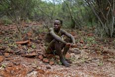 A young Pokot man sits on the ground after having been smeared with the contents of a bull's stomach by elders during an initiation ceremony in Baringo County, Kenya, January 20, 2016. REUTERS/Siegfried Modola