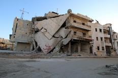 Разрушенное здание в городе Храйтан в сирийской провинции Алеппо. 3 февраля 2016 года. По меньшей мере 500 человек погибли с обеих сторон в ходе боев в сирийской провинции Алеппо с начала наступления правительственных войск Башара Асада и их союзников на удерживаемые повстанцами территории, сообщила в среду организация, отслеживающая ход войны. REUTERS/Abdalrhman Ismail