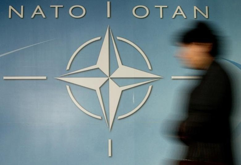 A woman walks past the NATO logo at the entrance of the Allianceheadquarters ahead of a NATO foreign ministers meeting in BrusselsDecember 4, 2003. REUTERS/Thierry Roge