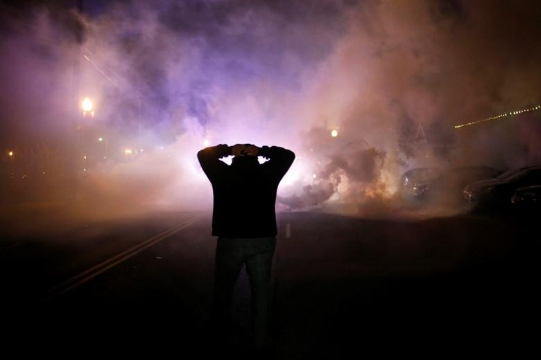 A protester stands with his hands on his head as a cloud of tear gas approaches after a grand jury returned no indictment in the shooting of Michael Brown in Ferguson, Missouri, in this November 24, 2014 file photo. REUTERS/Adrees Latif/Files