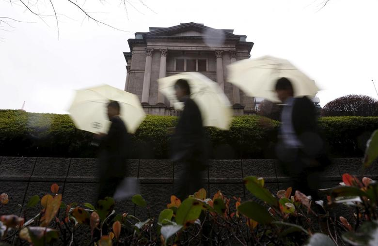 Pedestrians holding umbrellas walk in front of the Bank of Japan headquarters in Tokyo, Japan January 29, 2016. REUTERS/Yuya Shino