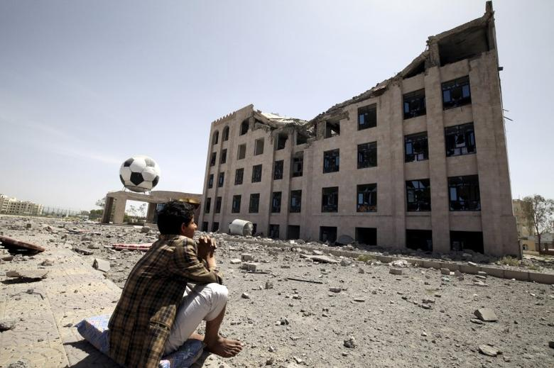 A Houthi militant sits amidst debris from the Yemeni Football Association building, which was damaged in a Saudi-led air strike, in Sanaa, May 31, 2015. REUTERS/Mohamed al-Sayaghi