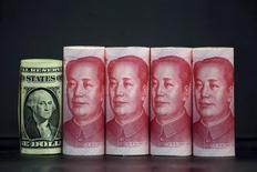 Chinese 100 yuan banknotes and a U.S. one dollar banknote are seen in this picture illustration in Beijing, China, January 21, 2016. REUTERS/Jason Lee