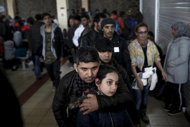 Refugees and migrants line up to receive a meal inside a terminal, moments after arriving aboard the Tera Jet passenger ship at the port of Piraeus, near Athens, Greece, February 10, 2016. REUTERS/Alkis Konstantinidis