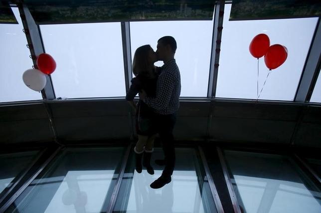 2月8日、愛情とお金という問題に関して、それが上手く調和するかどうかの展望は「何を伝えたか」で決まるとは限らない。「何を秘密にしているか」も重要なのだ。写真は13日、バレンタインデーの前日にモスクワのオスタンキノ・タワー展望台でキスをするカップル(2016年 ロイター/Maxim Shemetov)