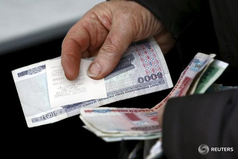 A woman holds Belarussian roubles as she buys products at the Belarussian Republican Union of Consumer Societies' mobile shop on the outskirts of Minsk, Belarus, December 23, 2015.  REUTERS/Vasily Fedosenko