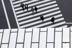 Los tipos de interés negativos del Banco de Japón entraron en vigor el martes en un plan radical que los operadores ya consideran un fracaso, lo que subraya la falta de opciones de Tokio para estimular el crecimiento en momentos en que los mercados globales se debilitan. En la imagen, peatones cruzan la calle en un distrito empresarial de Tokio, el 16 de febrero de 2016. REUTERS/Thomas Peter