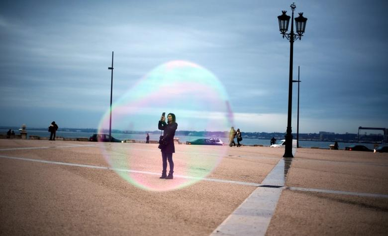 A tourist is seen through a soap bubble as she takes a picture at Comercio square in downtown Lisbon November 18, 2014.  REUTERS/Rafael Marchante