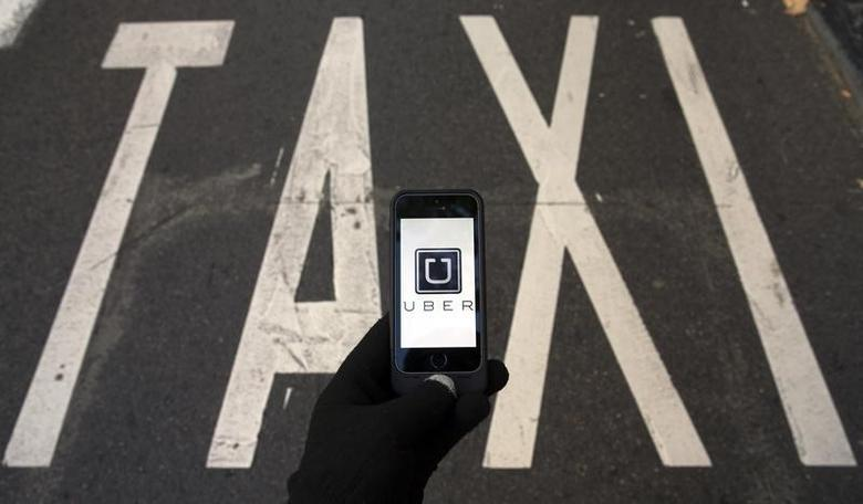 The logo of car-sharing service app Uber on a smartphone over a reserved lane for taxis in a street is seen in this photo illustration taken in Madrid on December 10, 2014.  REUTERS/Sergio Perez