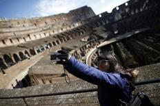 A woman takes a picture of herself in Rome's ancient Colosseum January 18, 2013.  REUTERS/Tony Gentile/Files